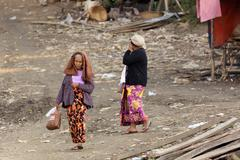 Senior Burmese woman walking in slum Stock Photos