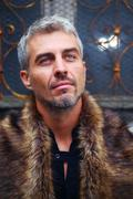 Portrait of a sexy man in wolf  fur and ornamental medieval window on background - stock photo