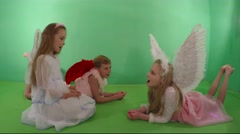 Two cute girls and a boy dressed as an angel sing. - stock footage