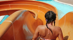 Young Woman, Girl Riding On Orange Water Slide To The Pool. Aquapark, Water Park - stock footage