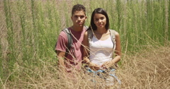 Serious Hispanic couple standing in shrubs - stock footage