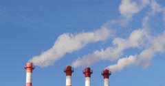 Factory in the City. From the pipes of the plant goes white smoke. The plant is Stock Footage