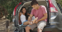 Young mixed ethnic man wrapping girl's ankle with bandage - stock footage