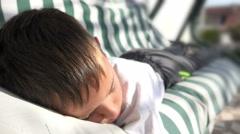 Sleepy boy sleep swinging on garden bed Stock Footage