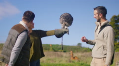 4K Visitors to a falconry centre handling & learning about Verreaux's eagle owl Stock Footage