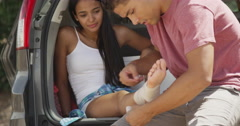 Good looking hispanic man helping injured girlfriend Stock Footage