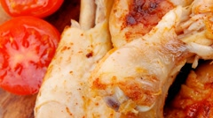 Grilled chicken drumstick with tomatoes and thyme on wooden plat Stock Footage