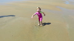 Baby jumping puddle at beach slowmotion Stock Footage