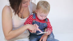 Young mother and kid son playing with mobile phone Stock Footage