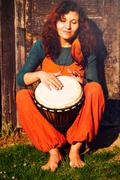 Young barefoot lady drummer playing on her djembe drum on rustic wooden door - stock photo