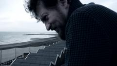 Angry sad man crying in front of the ocean - stock footage