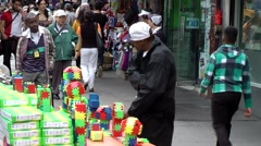 New York City 482 Chinatown district; street trader with colorful toys Stock Footage