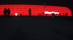 Silhouettes of tourists night football stadium with background glow red Stock Footage