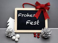 german 'Frohes Fest' (Merry Christmas) on blackboard - stock photo