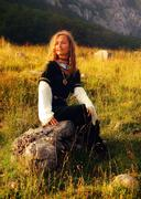 Mystical medieval maiden sitting on a wild meadow stone in a mountain landscape Stock Photos