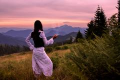 Mystic woman in ancient dress alone in a romantic sunset landscape Stock Photos