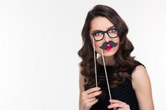 Comical curly young female playing with glasses and moustache booth - stock photo