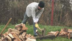 Lumberjack cutting wood logs with axe - stock footage