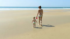 mother and baby walking with bucket at beach - stock footage