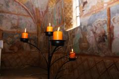 Candles burning on black candleholder inside ancient fresco walls Stock Photos
