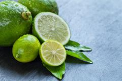 Fresh limes place on black stone - stock photo