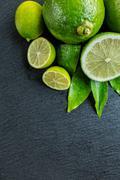 Fresh limes place on black stone Stock Photos