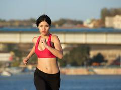 Healthy young sports woman running outdoors - stock photo