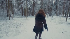 Girl running in the winter forest. She turns, whirls and throws snow. Arkistovideo