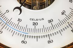 Close up of a vintage circular thermometer - stock photo