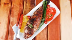 Whole fried bass on plate over wood Stock Footage