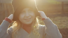 Happy little girl pulling his cap over his eyes on a background of nature Stock Footage