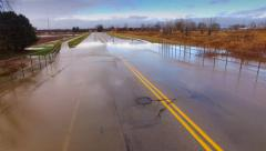 Muddy flood waters overrun roadway Stock Footage