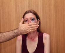 Beaten up woman with bruises on her face and male hand covering her mouth Stock Photos