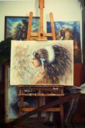 Airbrush painting of a young native indian woman in painting atelier Stock Photos