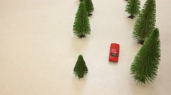 On table among trees toy move two cars and one comes to house Stock Footage