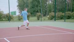 Tennis player uses backhand slice on the half court. Slow motion - stock footage