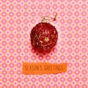 Stock Photo of christmas ball and text seasons greetings on a colorful background