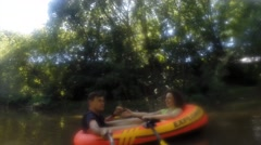 Couple floating on a rubber boat on the canal in the summer. Stock Footage