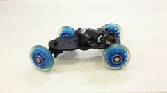 Dolly with blue wheels moves at light table. Stop motion. Stock Footage