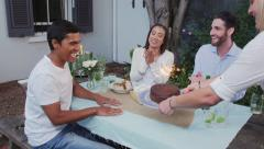 Cake with sparklers carried to table of friends for birthday celebration fun in  - stock footage