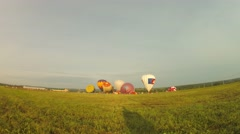 Grass field with colorful air balloons which begin fly Stock Footage