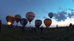 Several air balloons on field with many people at summer Stock Footage