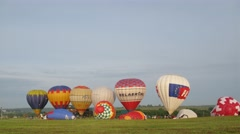 Several of colorful air balloons start fly from grass field Stock Footage