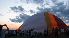 People stay in the field where inflated air balloons at evening Stock Footage