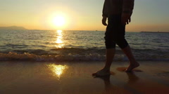 4K panning man running in shallow sea at sunset 3840x2160 - stock footage