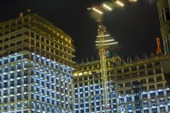 Lots of tower cranes build large residential buildings at night. buildings un - stock photo