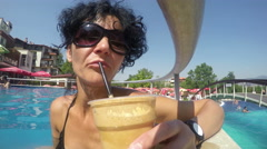 Pretty female model drinks caffee in thermal pool Stock Footage