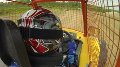 Boy riding go-cart, driver is protected by a mesh. Stock Footage