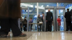 People pass through a gate to the hall, guard conducts inspections Stock Footage