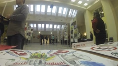 Exhibition of drawings in the hall, visitors walk and look Stock Footage